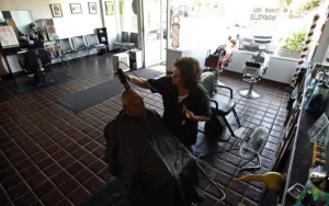 Michele Casco gives a haircut to Charlie Iantosca of Denville at the Family Barber Shop on Broadway in Denville. The shop is still without power but used generators as residents and business owners in Denville, NJ start the cleaning and recovery process after Hurricane Irene flooded the downtown area._8/31/11_STAFF PHOTOGRAPHER/BOB KARP_2011 / staff photo